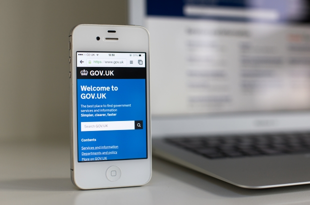 GOV.UK on a mobile phone with a laptop in the background