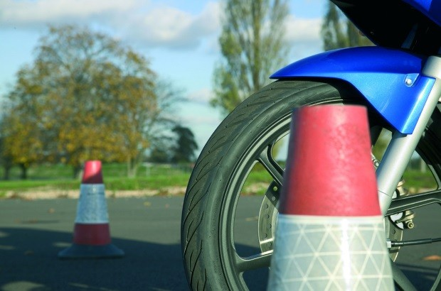 Motorcycle wheel next to cones on motorcycle pad