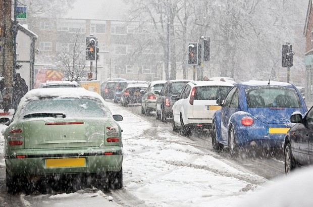 Cars driving in snow at a set of traffic lights