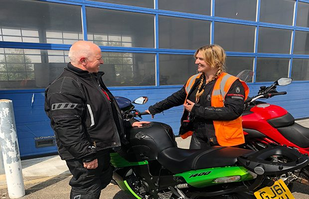 An ERS trainer and pupil standing either side of a motorcycle, smiling at each other