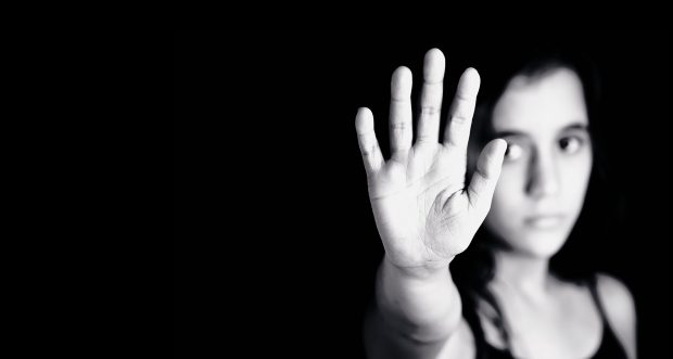 Girl in black and white holding her hand to the camera