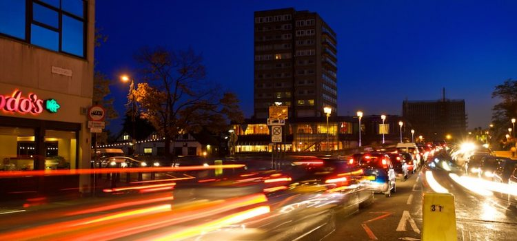 Cars driving down a busy main road in a town centre, in the dark with their lights on.